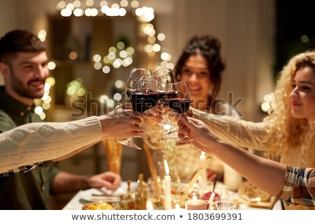 happy friends drinking red wine at christmas party Stock photo © dolgachov