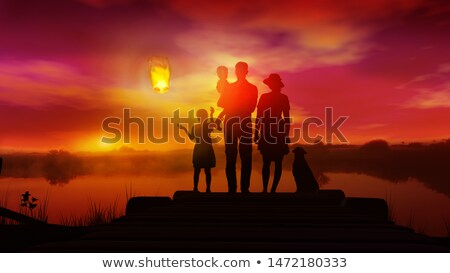 Family with children watches on launched Chinese lantern at sunset Stock photo © ConceptCafe