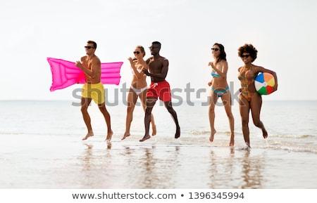 Vrienden lopen strandbal zwemmen matras vriendschap Stockfoto © dolgachov