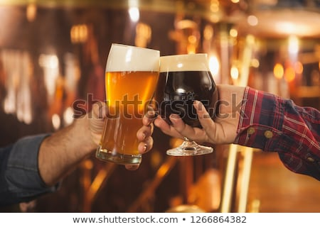 brewers clinking glasses of craft beer at brewery stock photo © dolgachov