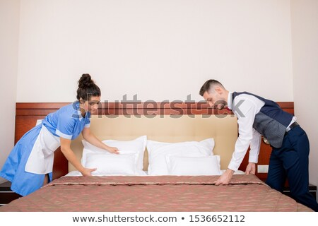 Young porter and chamber maid bending over bed while making it in the morning Stock photo © pressmaster