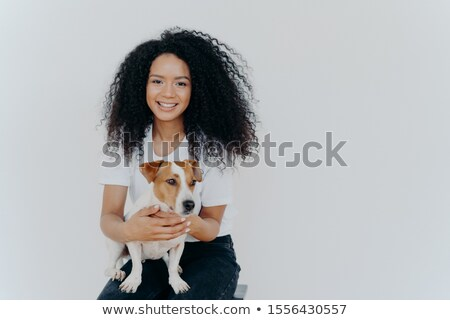 Humans and animals concept. Cheerful good looking woman with crisp hair, smiles pleasantly, plays wi Stock photo © vkstudio