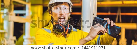 BANNER, LONG FORMAT Young man in a yellow work uniform, glasses and helmet in industrial environment Stock photo © galitskaya