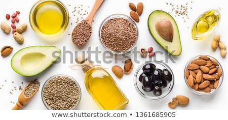 Bowl of raw natural organic linseed flaxseed oil and omega 3 capsules on light table background. Stock photo © DenisMArt