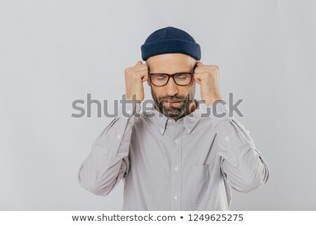 People, tension and migraine concept. Depressed unshaven young male suffers from headache, keeps han Stock photo © vkstudio