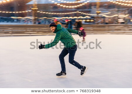 Male in speed demonstrates his skills of skating, has fun on rin Stock photo © vkstudio