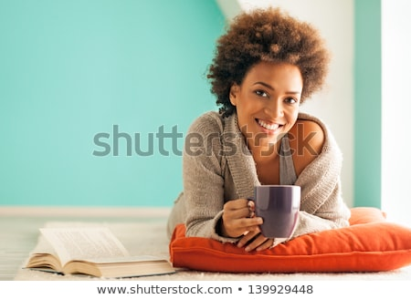 Close-up of a young woman smiling and drinking coffee stock photo © stokkete