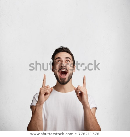 Stock photo: Young male pointing upwards against a white background