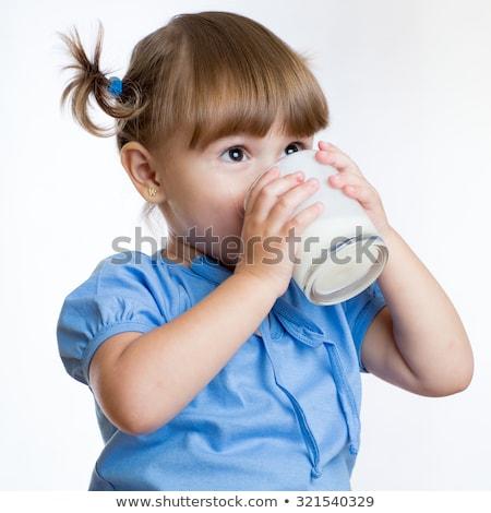 笑みを浮かべて · 女の子 · 飲料 · ミルク · 外に · ガラス - ストックフォト © dolgachov