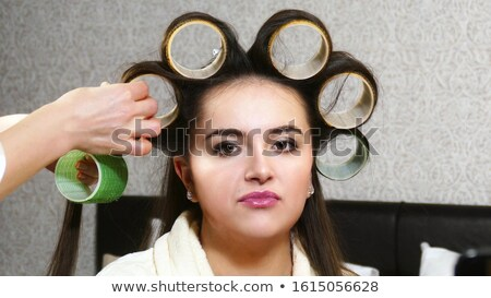 Woman hairdresser taking off curlers from long hair of female  Stock photo © deandrobot