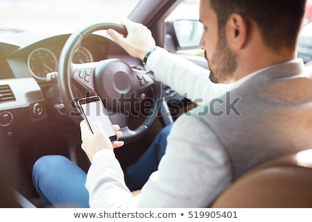 Man using mobile phone while driving his car Stock photo © deandrobot