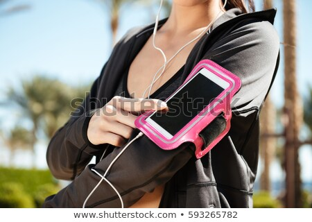 Woman athlete using cell phone in armband on summer resort Stock photo © deandrobot