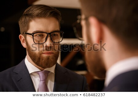 Concentrated young bearded businessman looking at mirror. Stock photo © deandrobot