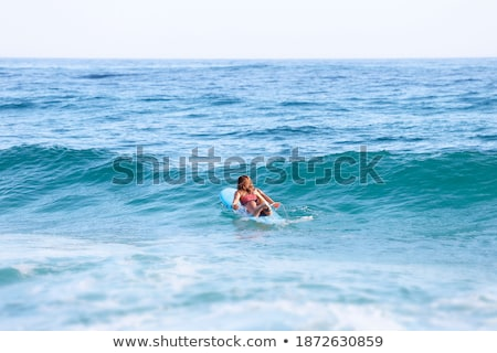 Female surfer paddling on surfboard to the open sea Stock photo © Kzenon