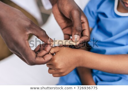african american doctor putting adhesive plaster Stock photo © LightFieldStudios