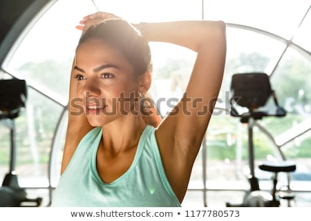 Picture of Pleased sports woman warming up and looking away Stock photo © deandrobot