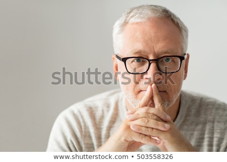 close up of senior man in glasses thinking stock photo © dolgachov