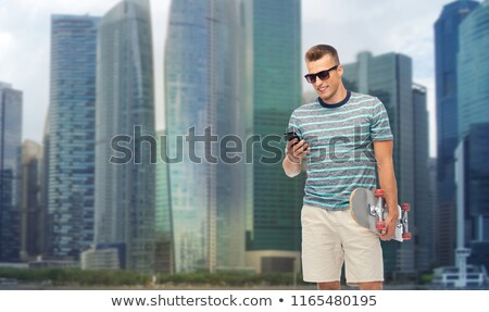 man with skateboard and smartphone over singapore Stock photo © dolgachov