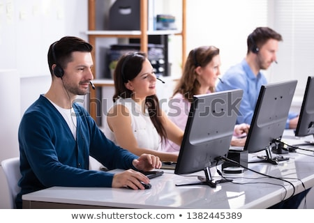 smiling customer service executives using earphones stock photo © andreypopov