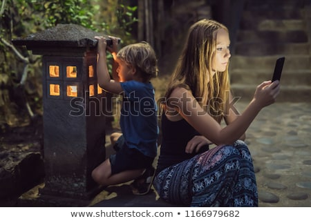 Mom looks into her smartphone, the son looks into the luminous cozy window of the house. The boy lac Stock photo © galitskaya