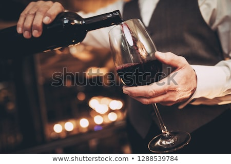 elegant glass and bottle of red wine with corks and corkscrew on dark wooden background natural lig stock photo © denismart
