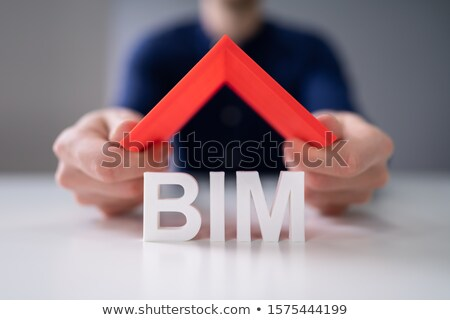 Human Finger Holding Roof With BIM Text On Desk Stock photo © AndreyPopov