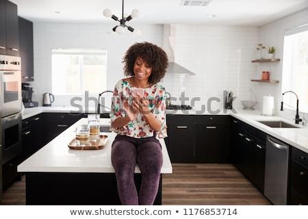 Mulher telefone móvel cozinha casa computador laranja Foto stock © wavebreak_media