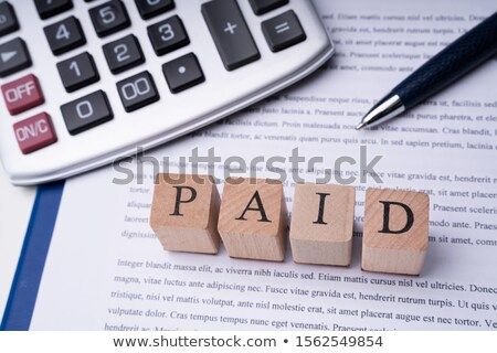 Paid Text On Blocks Over Documents With Calculator And Pen Stock photo © AndreyPopov