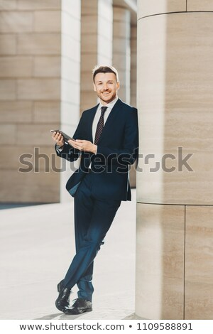 Photo of cheerful male dressed in expensive black suit, stands crossed legs, works on touch pad, sta Stock photo © vkstudio