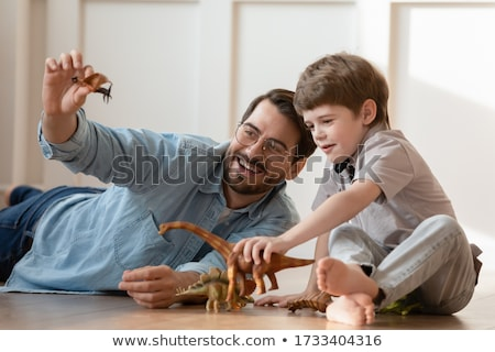 father and son playing with toy dinosaur at home Stock photo © dolgachov
