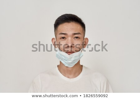 Horizontal shot of young man in medical mask prevents infectious pneumonia, coronavirus pandemic, vi Stock photo © vkstudio