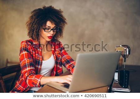 portrait of a smiling young business woman using laptop at outdo stock photo © hasloo