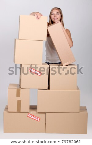 Young woman with a pile of cardboard boxes marked fragile Stock photo © photography33