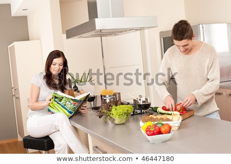 Young couple in a kitchen with a cookbook stock photo © photography33