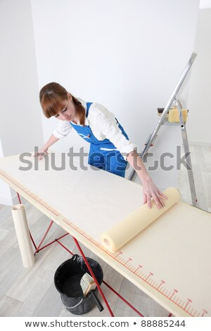 Woman laying wallpaper out on a pasting table Stock photo © photography33