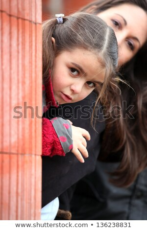 Mother and daughter peering from behind brick wall Stock photo © photography33