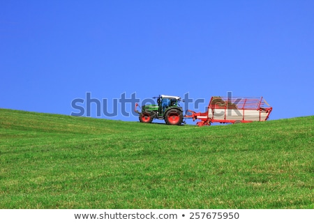 Tractor pulling trailer in a harvested field Stock photo © sarahdoow