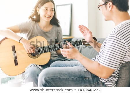 Young Man Relaxing Sitting On Sofa Playing Acoustic Guitar Stock photo © monkey_business