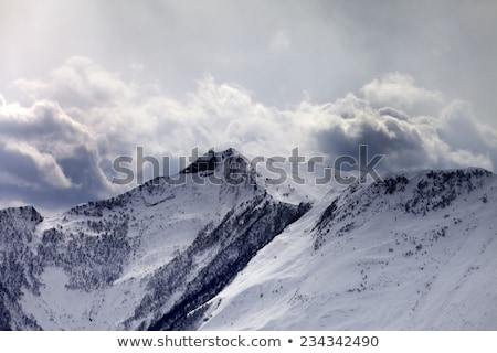 Sunlit off-piste slope and mountains in dark clouds Stock photo © BSANI