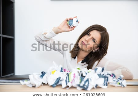 Angry businesswoman sitting at the table with trash paper Stock photo © deandrobot