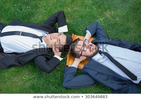 the two happy young businessmen in a suit lying on the green grass stock photo © master1305
