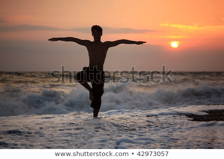 Stock photo:  Silhouette guy yoga on sunset wavy beach