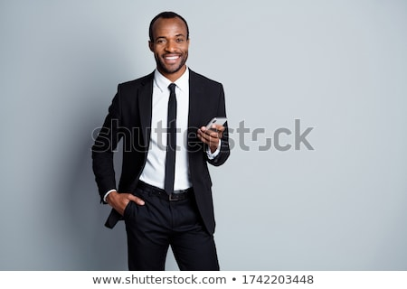 Smiling man in black jacket over gray background Stock photo © ozgur