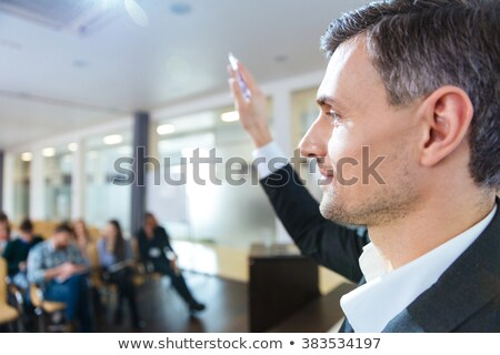 Serious speaker standing with raised hand on business meeting  Stock photo © deandrobot
