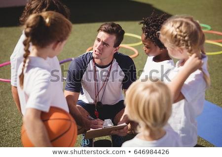 Trainer interacting with schoolkids Stock photo © wavebreak_media