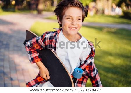 smiling male teenager guy holding skateboard stock photo © deandrobot
