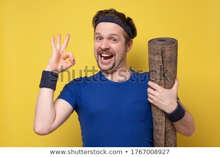 Cheerful young sports man posing showing ok gesture. Stock photo © deandrobot