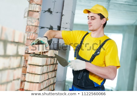 professional construction worker laying clay bricks blocks and b stock photo © milsiart