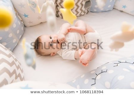 Baby boy playing in thecrib with mobile toy Stock photo © Lopolo