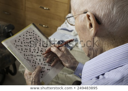 Stock photo: A elderly man sitting doing crosswords hobby